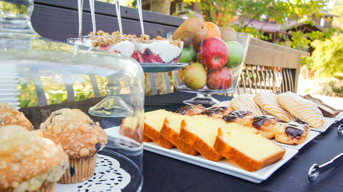 Light breakfast spread of pastries, muffins, fruit, and parfaits during Music & Mimosas event