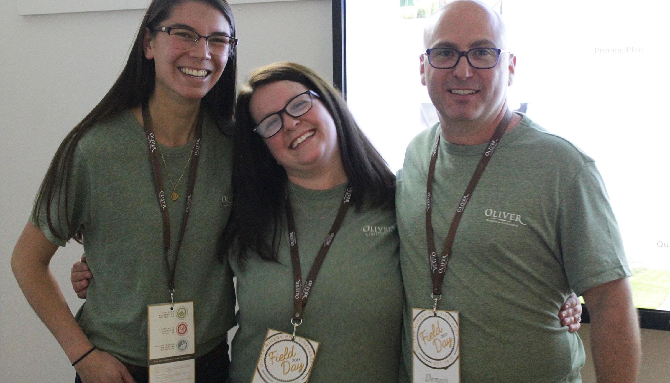 Three employees pose for a picture wearing Oliver Winery Field Day T-shirts and nametags.