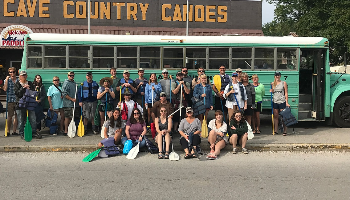 "Large group of Oliver Winery staff members gathered with oars and life jackets in front of a bus and a ""cave country canoes"" sign."